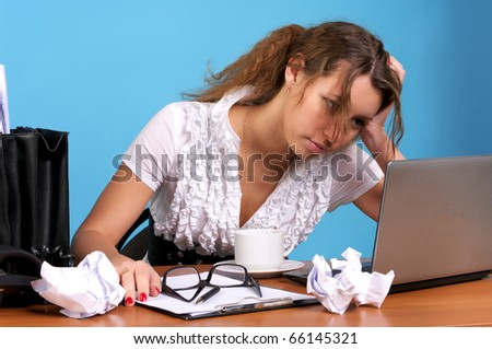 Beautiful young employer looking at laptop with troubled expression - stock photo