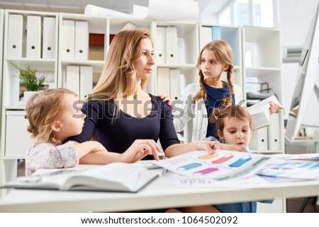 Beautiful young entrepreneur sitting at desk and working on ambitious project while her little children trying to attract her attention, interior of modern office on background