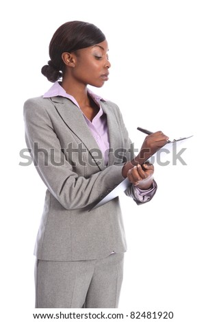 Beautiful young ethnic african american business woman holding clipboard and writing using black pen. She is looking down at the paper with a serious expression.
