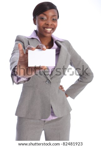 Beautiful young ethnic african american business woman with a big happy smile, holding out a business card. Model is blurred in background with card in sharp focus close to camera.