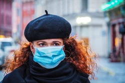 Beautiful young European woman in spring clothes on the street with a medical face mask on. Closeup of a 30-year-old female in a respirator to protect against infection with coronavirus - Covid19