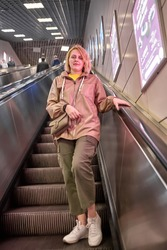 Beautiful young European woman walks down to subway station while standing on steps of escalator.