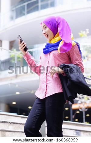 Beautiful young executive using tablet phone outdoor excited expression - stock photo