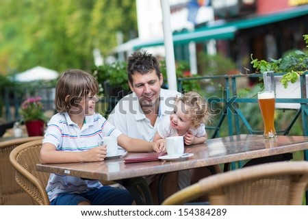 Beautiful young family - a father and two children, adorable baby girl and a school boy, laughing and talking enjoying a drink in an outside cafe in summer in an old city center in Germany