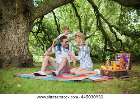 Beautiful young family with a small boy in checkered blankets resting in the park with wicker basket filled with food and drink. Following, fun, pictures
