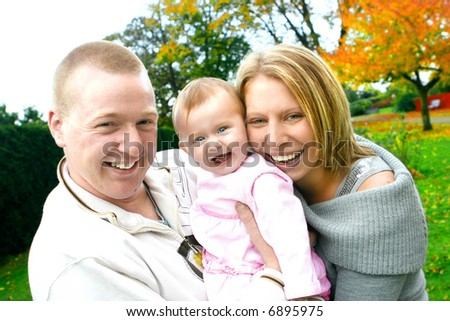 Beautiful young family with baby girl in an autumn park - stock photo