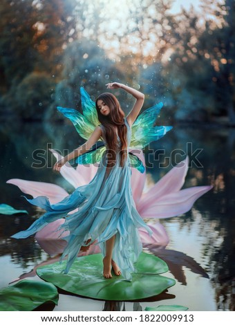 Beautiful young fantasy woman in image river fairy dances on water pink lily flower. long silk dress flies in wind motion butterfly wings magic shiny. Art Girl pixie. Background dark nature, blue lake Сток-фото ©
