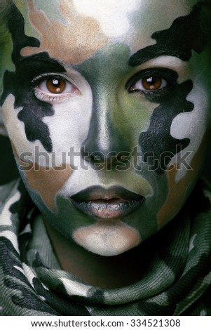 Beautiful young fashion woman with military style clothing and face paint make-up, khaki colors, halloween celebration swag close up