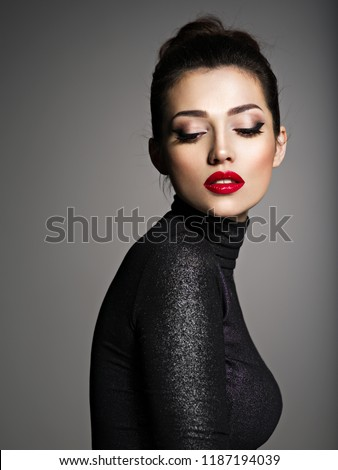 Beautiful young fashion woman with red lipstick. Glamour fashion model with bright gloss make-up  posing at studio.