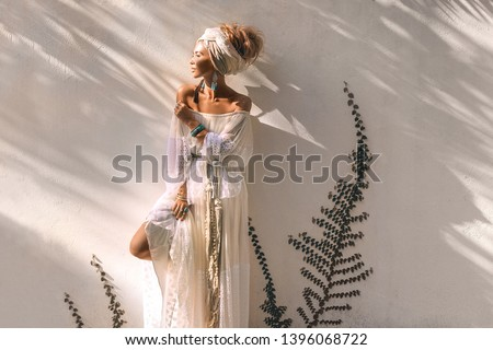 beautiful young fashionable woman in turban outdoors at sunset