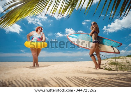 Beautiful young fat woman and skinny girl on the summer beach