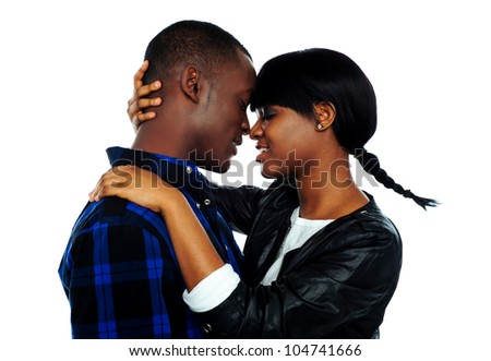 Beautiful young female about to kiss her boyfriend against white background