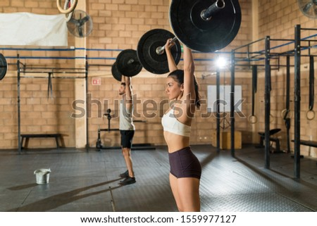 Beautiful young female athlete lifting barbell with male friend at health club