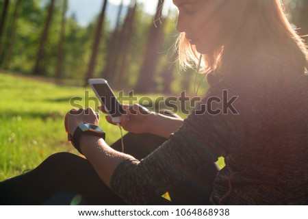 Beautiful young female athlete using fitness app on her smart watch to monitor workout performance. Lifestyle wearable technology concept with lensflare.