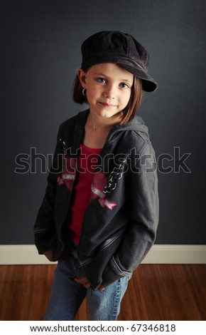 Beautiful young female child wearing a newsboy cap and ripped jeans