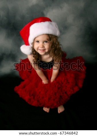 Beautiful young female child wearing a santa hat and red tutu skirt