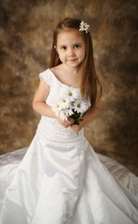 Beautiful young female child wearing her mother's wedding dress which is too big for her