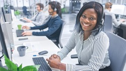 Beautiful Young Female Customer Service Operator Smiling for a Portrait at a Busy Modern Call Center with Diverse Multicultural Team of Office Specialists Wearing Headsets and Taking Calls.