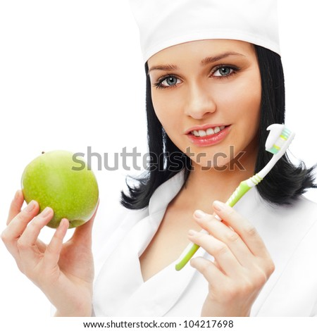 Beautiful young female dentist doctor with a toothbrush and green apple. Dental care concept