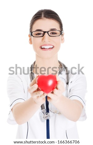 Shutterstock Beautiful young female doctor holding a heart. Isolated on white.