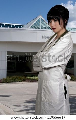Beautiful young female doctor outside of a hospital