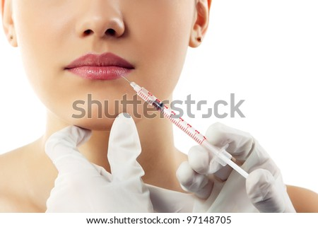 beautiful young female face and hands in gloves with beauty treatment injection in lips isolated on white