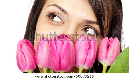 beautiful young female face behind bouquet of pink tulips