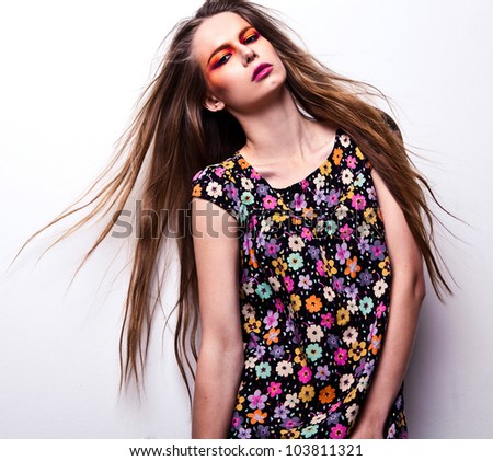 Beautiful young female face with bright fashion multicolored make-up.