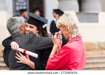 beautiful young female graduate hugging her father at graduation