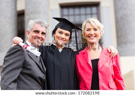 beautiful young female graduate with parents at ceremony