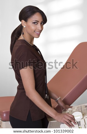 Beautiful young female nurse poses with an ultrasound machine.