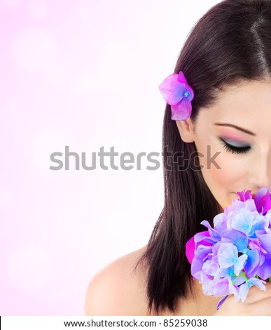 Beautiful young female portrait, hand holding a purple flower, isolated on pink background, beauty and spa concept