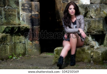 Beautiful young female posing in old stone ruins