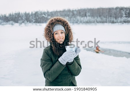 Beautiful young female smiling and drinking tea in nature Winter swimming. Woman in frozen lake ice hole. Swimmers wellness in icy water. How to swim in cold water Gray hat and gloves swimming clothes
