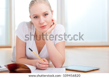 Beautiful young female student taking notes while studying, lying on the floor with tablet computer beside her and looking into the camera