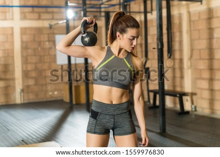 Beautiful young fit female athlete exercising with kettlebell on shoulder while looking down at health club