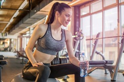 Beautiful young fit girl holding water bottle and resting on fitness ball after training in the gym.