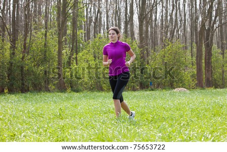Beautiful young fit girl running outdoors in the meadow