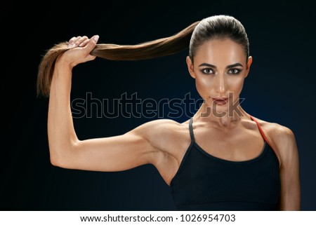 Beautiful young fit sexy woman in sportswear holding her ponytail over black background Strong healthy hair Clipping path Female bodybuilder with power hand confidental looking forward