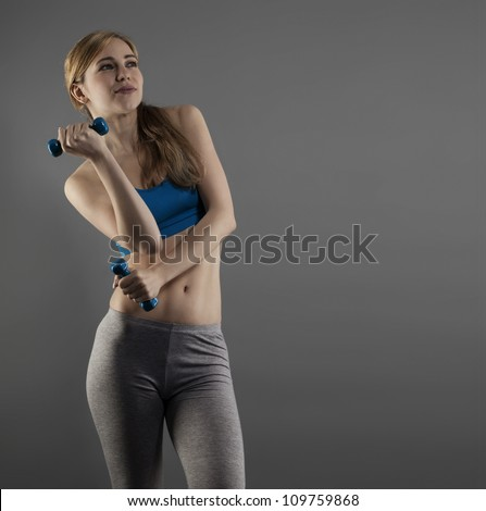 beautiful young fitness woman with dumbbells on grey background