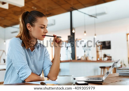 Beautiful Young Freelancer Woman Using Laptop Computer Sitting At Cafe Table. Happy Smiling Girl Working Online Or Studying And Learning While Using Notebook. Freelance Work, Business People Concept