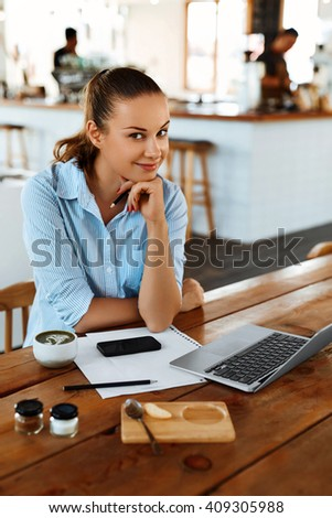 Beautiful Young Freelancer Woman Using Laptop Computer Sitting At Cafe Table. Happy Smiling Girl Working Online Or Studying And Learning While Using Notebook. Freelance Work, Business People Concept   - Shutterstock ID 409305988