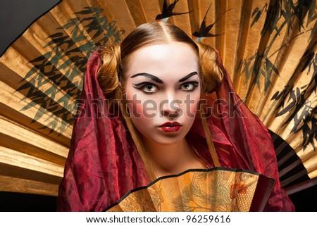 Beautiful young geisha girl, on grey background