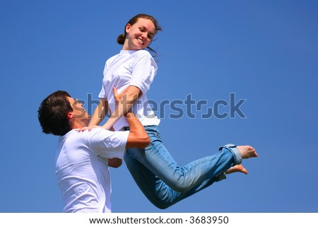 Beautiful young girl and young man have fun against bluee sky