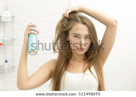 Beautiful young girl applying hair spray on her hair, choosing a new hairstyle, looking seriously at the mirror, home bathroom interior. Beauty concept photo, lifestyle