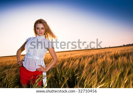 Beautiful young girl at golden field