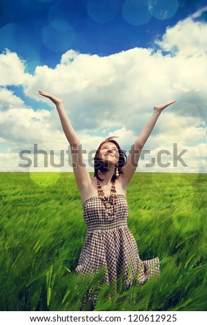 Beautiful young girl at green field