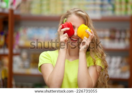 Beautiful young girl at the grocery store closed her eyes bell peppers