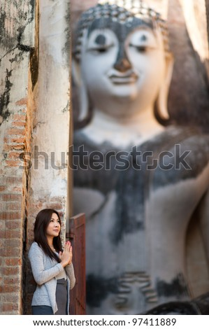 Beautiful young girl blessing big buddha at Srichum temple. Sukhothai - Thailand
