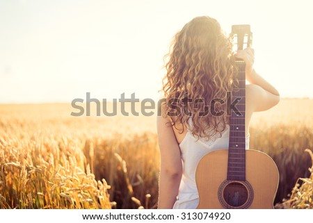Beautiful young girl carrying her guitar through the golden wheat field. Lens flare, selective focus, toned image.
